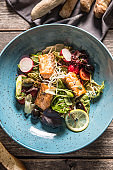 Fresh vegetable salad with roasted salmon olive oil and baguette