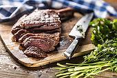 Freshly grilled tomahawk steak on slate plate with salt pepper rosemary and parsley herbs. Sliced pieces of juicy beef steak
