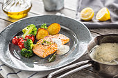 Roasted salmon fillet broccoli tomatoes and fried potatoes with dill cream sauce