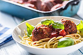 Delisious italian meal meat beef balls with pasta spaghetti and basil in white plate.