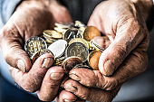 Pensioner man holding in hands euro coins. Theme of low pensions