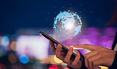 Technology iot (Internet of think), hand holding smartphone with modern circle global network for worldwide international connection, on bokeh colors light in night atmospheric city
