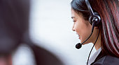 Back view of woman consultant wearing microphone headset of customer support phone operator at workplace.