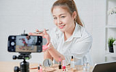 Young Asian woman beauty vlogger video online is showing make up on cosmetics products and live video on digital smartphone.