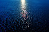 sun reflection in dark blue water in river