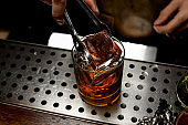 Bartender adds an ice cube in whiskey
