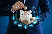 Financial and investment, Banking and saving, Businessman holding piggy bank and insert coin with icon on blue background