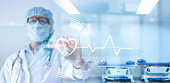 Cardiologist doctor with stethoscope holding heart shape in hand and icon heartbeat and medical network connection on modern virtual screen networking interface on hospital  background, service mind, patient and medical business technology concept.