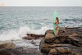 Slim fit girl in the multi colored swimsuit standing with the surf on the rocks on the beach