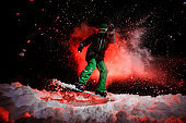 Girl on the snowboard dressed in a green sportswear jumping on the snow