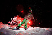 Active female snowboarder dressed in a green sportswear standind on the mountain hill