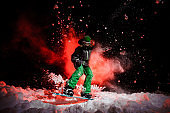 Active female snowboarder dressed in a green sportswear jumping on the snow
