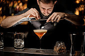 Bartender with beard pours an alcohol cocktail using grater