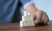 Health Insurance concept, Hand man stacking wooden block and arranging with icon healthcare medical, Life insurance of people.