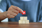 Hand holding wooden block and icon healthcare medical on table, Life insurance of people, Health insurance concept.