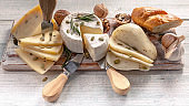 Food banner assorted fresh cheeses on a wooden board on wood background