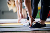 Women hands stretching to toecaps, group workout