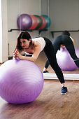 Woman doing exercise using sporting ball in gym