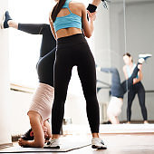 Trainer helping sporty woman to do handstand