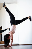 Young fit woman doing handstand exercise in gym