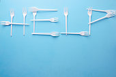 Word Help made of plastic forks on blue background