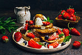 Stecked french toast topped with strawberries, blueberries, mint, ice cream and maple syrup