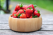 Sweet fresh juicy organic ripe strawberries in wooden bowl on wooden surface outdoors in garden or backyard