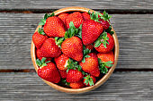 Sweet fresh juicy organic ripe strawberries in wooden bowl on wooden surface outdoors