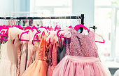 Rack with many beautiful holiday dresses for girls on hangers at children fashion showroom indoor. Kid girl dress hire studio for celebration birthday party or photography session event