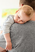 Portrait of cute adorable blond caucasian toddler boy sleeping on fathers shoulder indoors. Sweet little child feeling safety and care on daddys hand. Single father concept