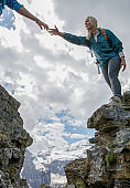 Woman reaches across a gap in the mountain to a helping hand