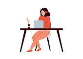 Happy woman sitting at desk and working on laptop computer