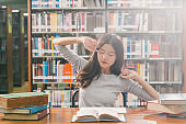 Asian young Student in casual suit reading and doing stretch oneself in library of university or colleage with various book and stationary on the wooden table over the book shelf, Back to school