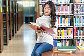 Asian young Student in casual suit reading the book in library of university or colleage on the wooden table over the book shelf background, Back to school concept