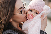 Portrait of mother and her little baby girl. Beautiful mom and cute baby. Mother hud her daughter. Baby dressed in peanch colour hat and nipple toy. Mom kiss her daughter