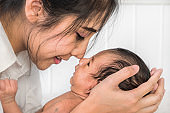 close up portrait of beautiful masian mother holding her infant baby boy on hands and kiss with nose