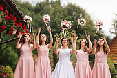 Happy bride with bridesmaid hold bouquets and have fun outside. Beautiful bridesmaid in same dresses stand by the charming bride in long wedding dress