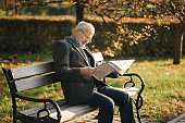 Handsome grandfather with a beautiful beard in a gray jacket sits on a bench in the park and reads a newspaper. Senior gray-haired man in glasses