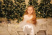 Little girl sitting on sleigh at home in front o Christmas trees. Winter holiday