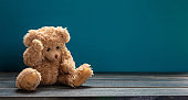 Teddy bear sad, sitting on the wooden floor, blue empty room background, copy space