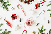 Christmas / New Year composition with fir branches, Christmas baubles, sweets, decorations on white background. Flat lay, top view colorful festive holiday concept