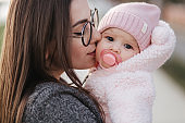 Portrait of mother and her little baby girl. Beautiful mom and cute baby. Mother hud her daughter. Baby dressed in peanch colour hat and nipple toy