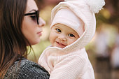 Portrait of cute little baby girl outside with mom. Beautiful girl smile. Five month baby. Happy family