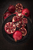 Fresh cuted pomegranates on the black plate on dark rustic background flat lay. 2