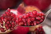 Spoon with pomegranate seeds on fresh ripe pomegranates background 2