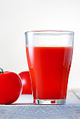 Glass of fresh tomato juice on wooden table.
