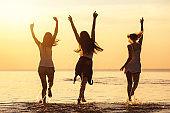 Three happy girls at calm sea beach and sunset