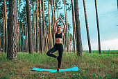 Beautiful athletic girl trained on yoga mat. Free space text. Active lifestyle nature. In leggings swimsuit. Fitness open air, harmony and gymnastics in concentration calm meditation infinity nature.