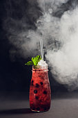 dark and stormy rum cocktail with Strawberry against background smoke.