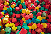 Many colorful soft blocks in a kids' pool at a playground. Bright multi-colored soft cubes, geometric toys. Multicolored background.